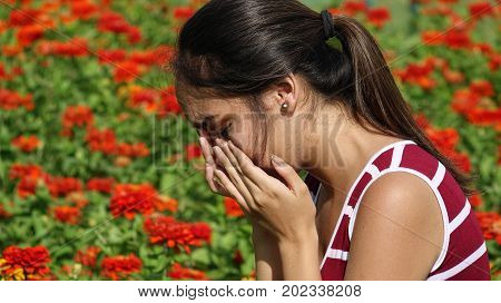 A Tearful Young Person Near Red Flowers