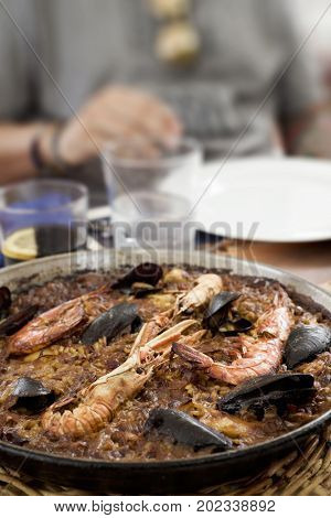 closeup of a paellera, the paella pan, with a typical spanish seafood paella on a table set for lunch and an unrecognizable young man seated to it