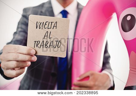 closeup of a young caucasian businessman wearing a swim ring in the shape of a pink flamingo showing a brown signboard with the text vuelta al trabajo, back to work written in spanish