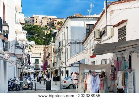 Ibiza Spain- June 10 2017: Tourists walking in the charming whitewashed narrow street in Ibiza old town. Balearic Islands. Spain