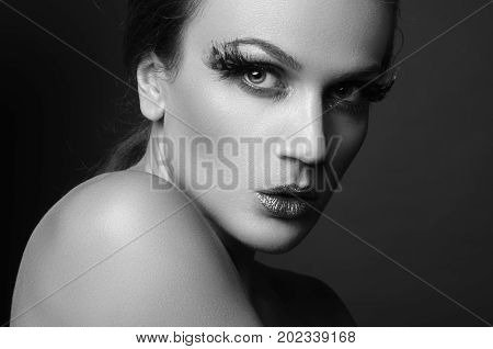 black and white beauty portrait of attractive woman with large patch of green feather eyelashes.