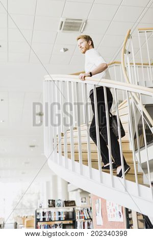 Handsome businessman walking down the stairs whilst holding a bag