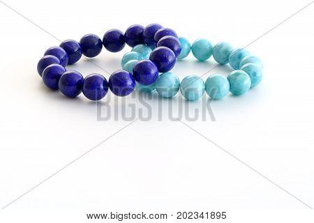 Beautiful high grade royal blue Lapis lazuli and light-blue Larimar or Stefilia's Stone beads in bracelets on white background