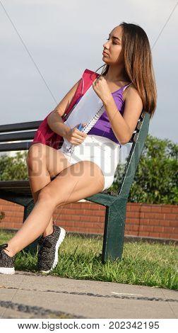Hispanic Female Student Sitting in a Park