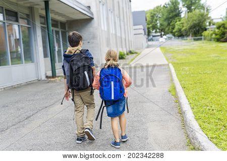 A Portrait of school 10 years boy and girl walk outside