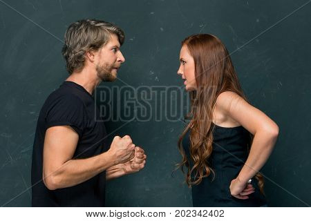 The conflict of couple - woman threatening and showing strength on dark background
