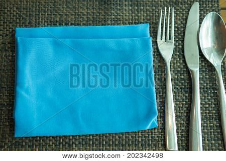 Silver tableware and blue napkin. Fork spoon and knife