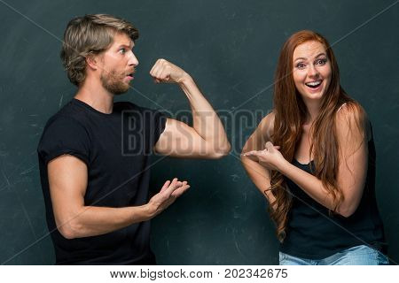 Beautiful woman impressed by the muscles of a bodybuilder, strong man showing off his muscles at studio on dark