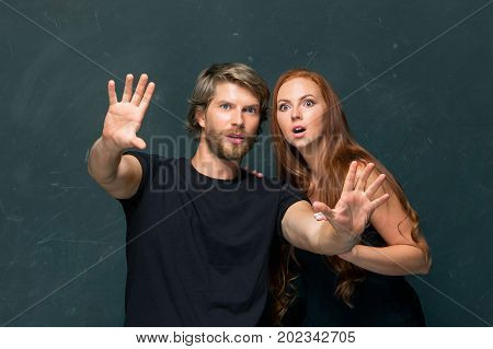 The surpried young Couple standing together at dark studio and looking at camera
