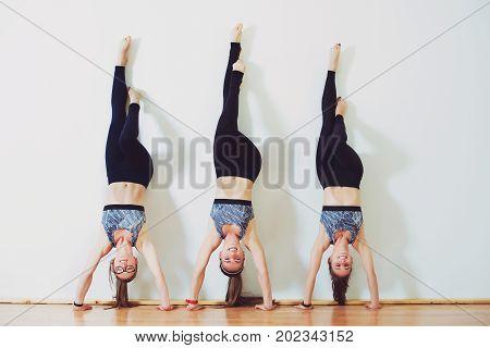 Three attractive young women doing handstand yoga asana in the sports studio Adho Mukha Vrksasana.