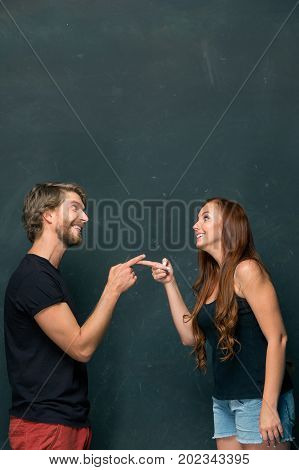 Young love Couple smiling and standing together at dark studio and looking at each other and pointing by finger