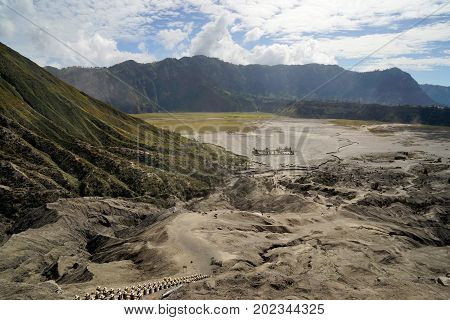 Panoramic view from the top of the stairs heading towards the dusty valley with buddhist temple at the foot of mount Batok at the Tengger Semeru National Park in East Java Indonesia.