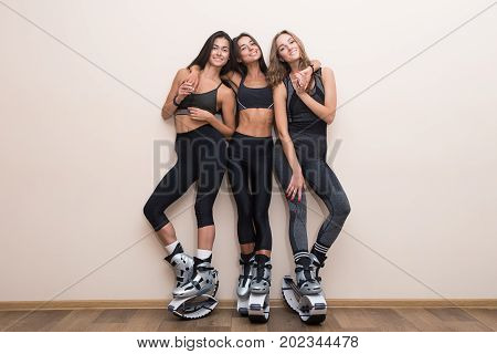 Team Of Happy Fitness Friends. Three Girlfrieds Posed In Kangoo Jumping Shoes. Sport Girl Standing O