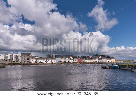 Galway Ireland - August 5 2017: LIne of colorful houses of The Long Walk quay under enormous white clouds in blue sky and with dark blue water of the port in front.