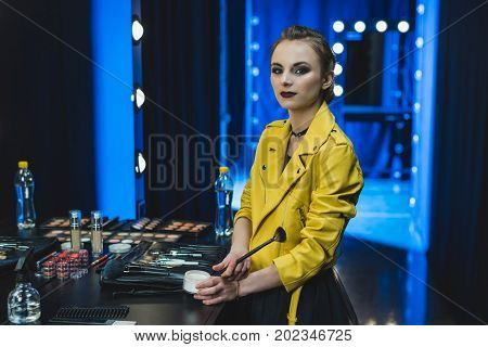attractive ballerina in yellow leather jacket applying makeup in dressing room