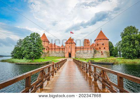 Trakai, Lithuania - August 15, 2017: Beautiful landscape of Trakai Island Castle, lake and wooden bridge, Lithuania. Trakai Island Castle and bright blue dramatic sky with clouds.