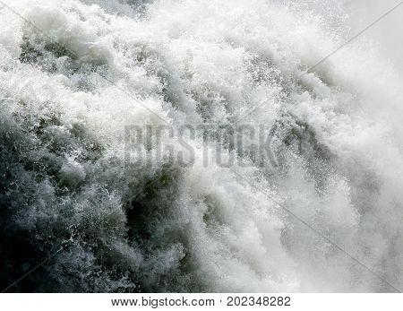 Raging waters of a big waterfall .