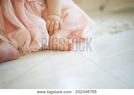 photo of little baby on the floor with drawn smiley face on her big toe