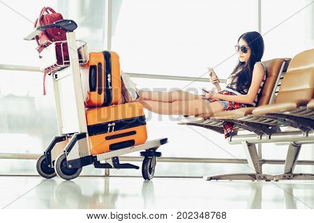 Young Asian traveler woman university student sit using smartphone at airport luggage and bag on trolley cart. Online check in mobile app study abroad or international tourism lifestyle concept