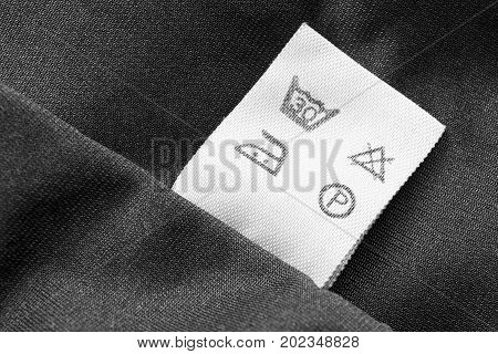 Washing instructions clothes label on black textile background