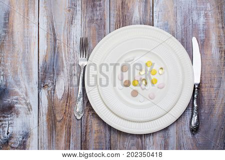 Plate with pills on wooden table. Space for text. Top view