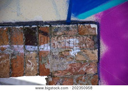 Photo of a wall detail with several colours and sunlight
