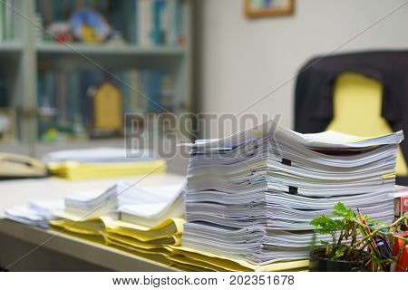 Pile of organized but unfinished business documents on desk in the office business and job concept