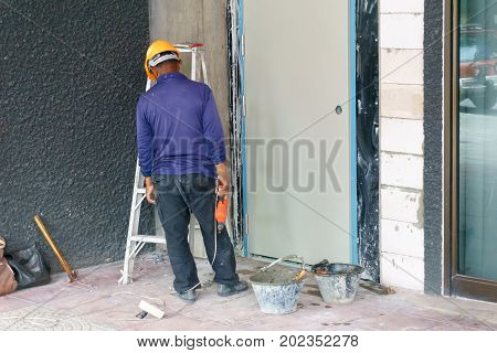 Construction Worker Wearing Yellow Safety Helmet Using Hammer And Chisel To Extract The Cement On Th