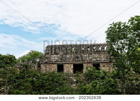 An image of the Temple of the Witch in the ancient Mayan city of Uxmal in the middle of the dense vegetation that envelops it with a background of a blue sky and clouds color ambient light