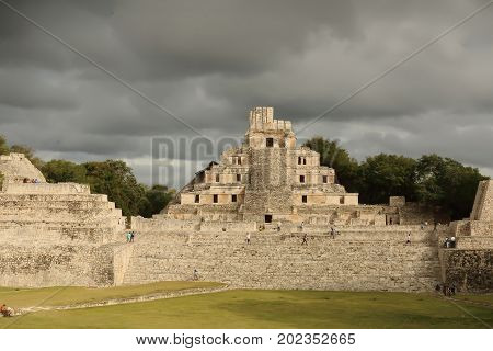 A beautiful image of the 5 level pyramid in the very old Mayan city of Edzna in the present Mexican state of Campeche with a background of blue sky and black clouds loaded with rain sunset light.