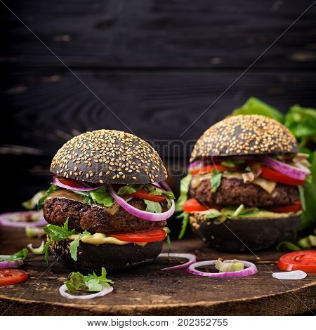 Black Big Sandwich -  Black Hamburger With Juicy Beef Burger, Cheese, Tomato,  And Red Onion On Blac
