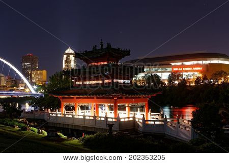 The John Deere Chinese Pavilion is one of the central features of the Chinese Cultural Center of America along the Des Moines River. The Wells Fargo Arena, Iowa Women of Achievement Bridge, and 801 Grand stand out in the background.