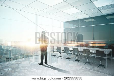 Back view of young businessman talking on the phone in modern conference room interior with city view and sunlight. Communication concept. Double exposure