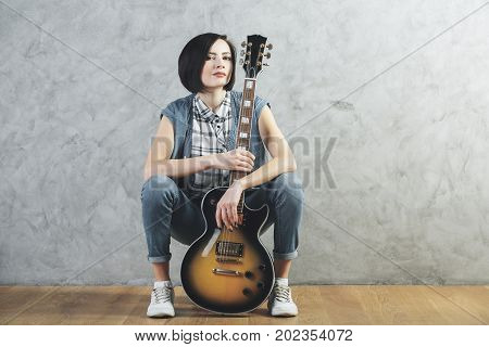 European woman with electric sunburst guitar and amplifier sitting in studio room with wooden floor and concrete wall. Musician concert hobby leisure rehearsal concept