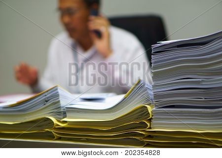 Pile Of Organized But Unfinished Business Documents On Desk With Businessman Talking On  Smartphone