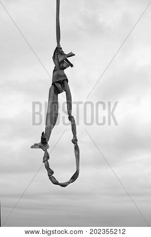 A noose made of old tow rope against the overcast sky vertical composition in black and white