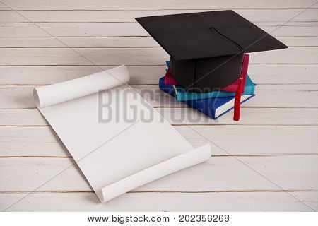 Mortarboard book and empty paper scroll on wooden surface. Graduation ceremony announcement concept. 3D Rendering