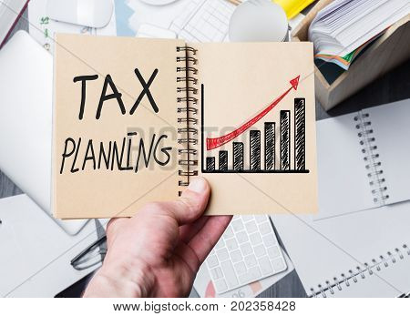 Hand holding notepad with text and chart above messy office desktop. Tax planning concept