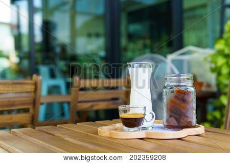 Iced Cube Coffee Latte With Milk And Shot Of Espresso On The Wooden Table In The Garden.