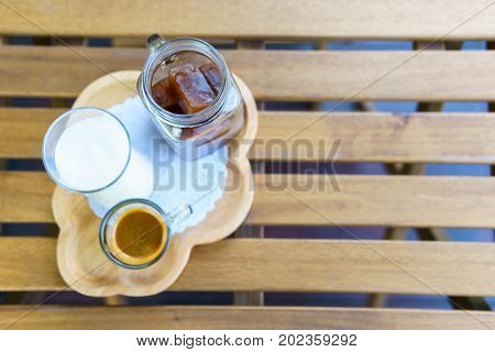 Top View. Iced Cube Coffee Latte With Milk And Shot Of Espresso On The Wooden Table In The Garden Wi