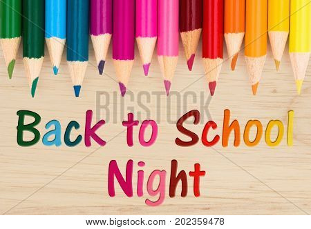 Back to School Night text with colorful pencil crayons on a wood desk