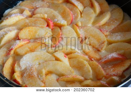 Raw charlotte with red apples and a sugar