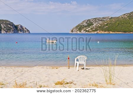 Beach with a white fisherman chair and a tied fishing boat at Porto Koufo harbor in Sithonia, Greece