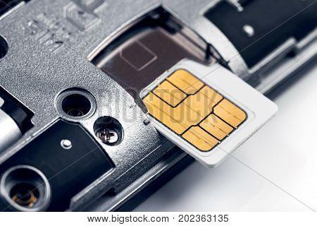 insert sim card in smart phone, macro shot poster