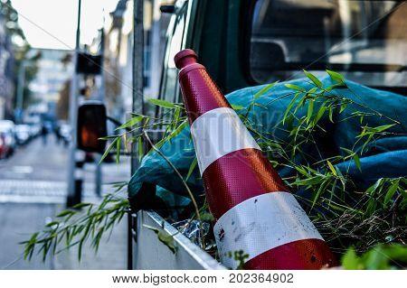 Pion in de bak van een gemeentewagen met groen.