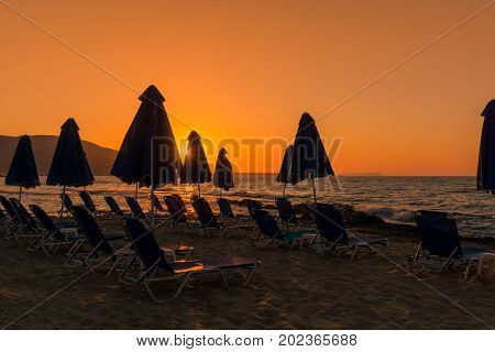 Deck Chairs and Sunshades in front of a Beach at Sunset. View on Deck Chairs and Sunshades at the Beach. Travel and Beach Background.
