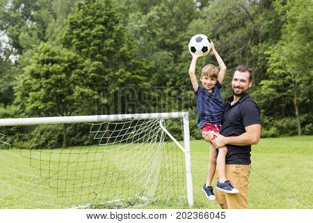 A father with son playing football on football pitch