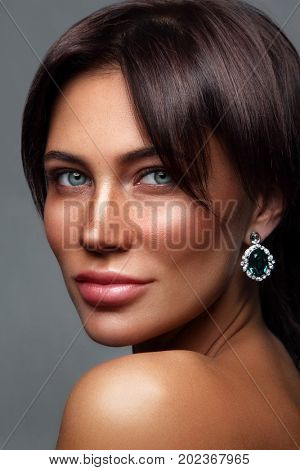 Portrait of young beautiful tanned woman with freckles