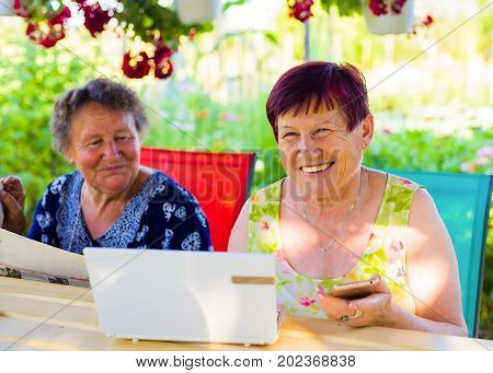 Happy elderly woman with successfully learn the use of network on laptop and mobile phone.