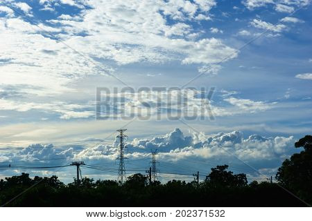panorama view of high voltage electricity pylon and transmission line with blue sky and cloud in the evening.
